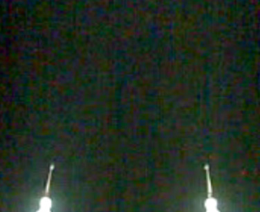 Mobile video still, showing the spires of the Petronas Twin towers during call to Ishak prayers at night.