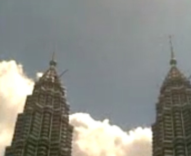 Mobile video still, showing the spires of the Petronas Twin towers during call to Azhar prayers at noon.
